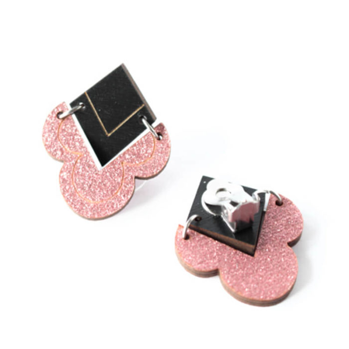 Desantran Kiteet malliston pinkin glitterin väriset korvakorut, joissa on musta yläosa. Korvakorut kiinnitetään korviin klipsuilla.