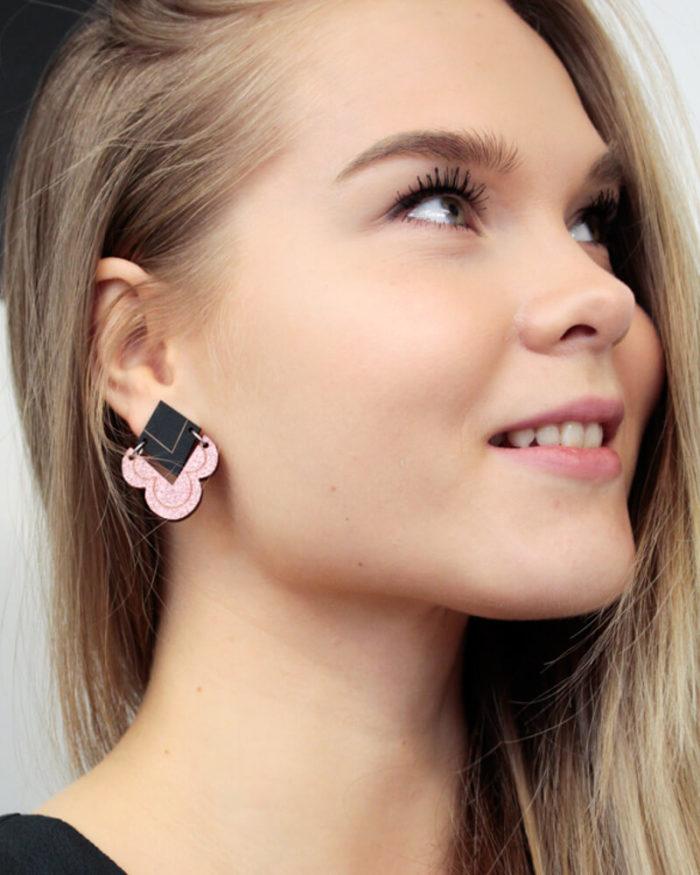 Desantran Kiteet malliston pinkin glitterin värinen korvakoru, jossa on musta yläosa. Korvakoruissa on klipsukiinnitys.