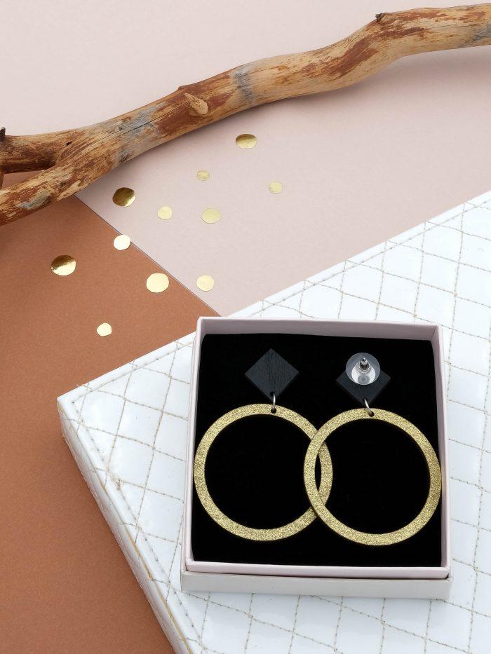 Halo korvakorut, joiden värit ylhäältä musta ja kultaglitter. Tappikiinnitys ja leveä silikoninen takaosa.