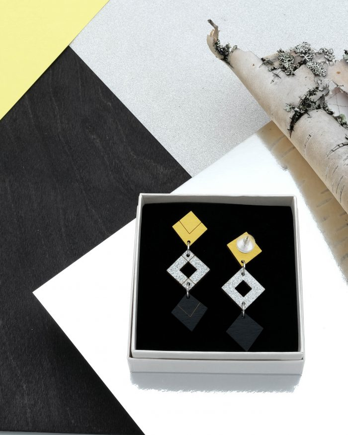 Palana kolmikko korvakorut, joiden väri ylhäältä keltainen, hopeaglitter ja musta. Tappikiinnitys.
